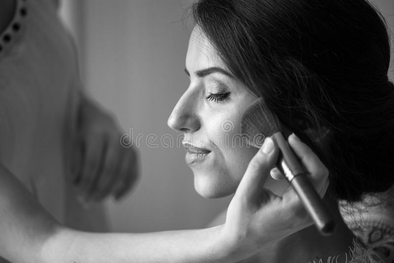 Pendant le matin, une femme est donnée le maquillage avant le mariage photo stock