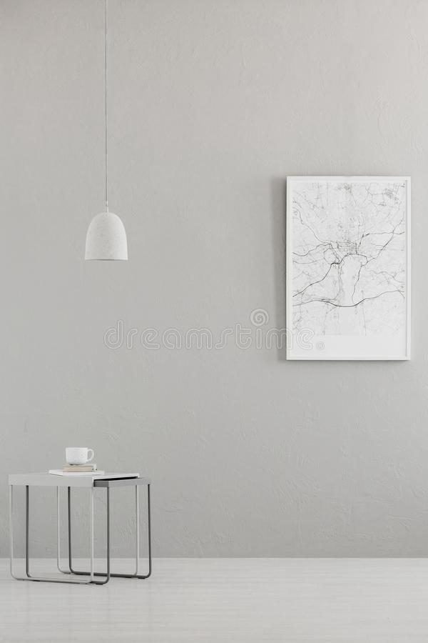 Pendant light above a modern table and a city map poster on a gray wall in a minimalist living room interior and place for a sofa. Real photo royalty free stock photography