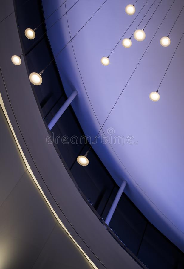 Modern Ceiling with pendant lighting. Pendant lights hang from a high atrium ceiling at an airport with a calming purple hue royalty free stock photos