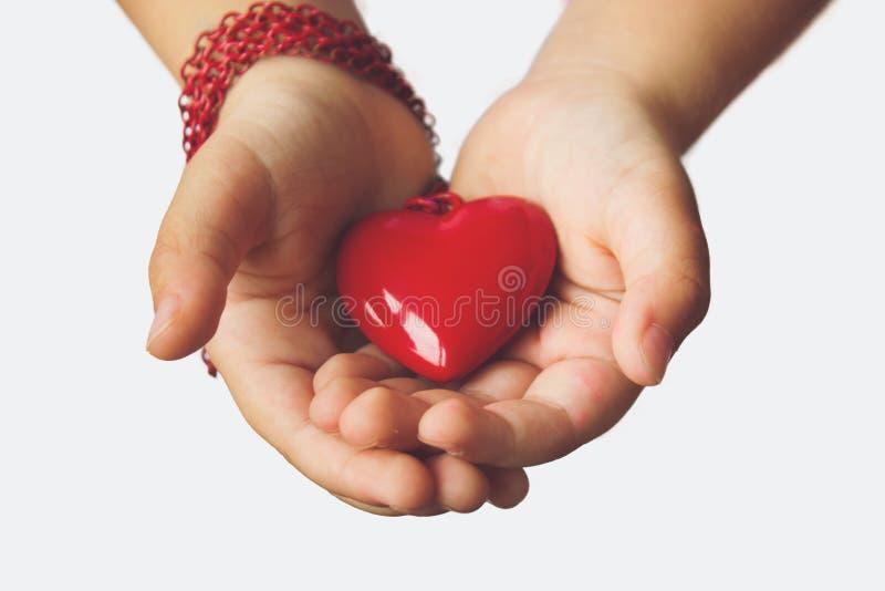 Pendant rouge de coeur sur des paumes du ` s de petite fille des mains images libres de droits