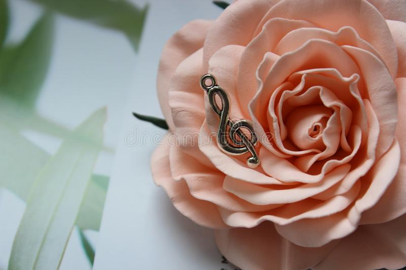 Pendant in the shape of a treble clef on a background of rose flower royalty free stock images