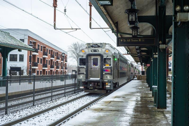 Pendeltåg som lämnar drevstationen efter snö arkivbild