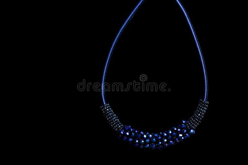 Pendente blu dei gioielli con i cristalli su fondo nero immagini stock