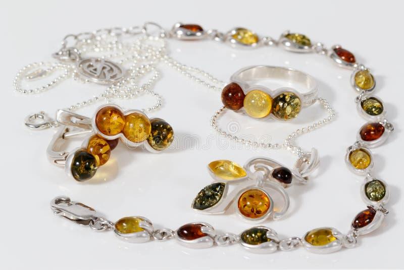 Pendente, brincos, anel e bracelete de prata do close up com âmbar Báltico na mesa acrílica branca imagens de stock