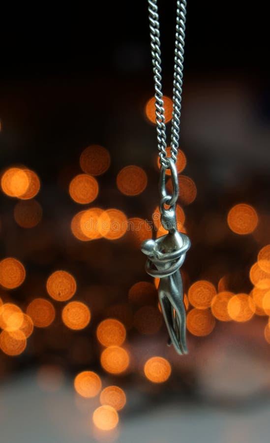 Pendente d'argento su una catena d'argento con il fondo del bokeh immagini stock libere da diritti
