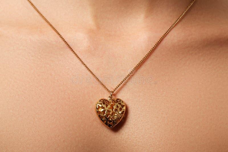 Pendente dourado do coração Beleza e conceito da joia Vestir da mulher fotografia de stock