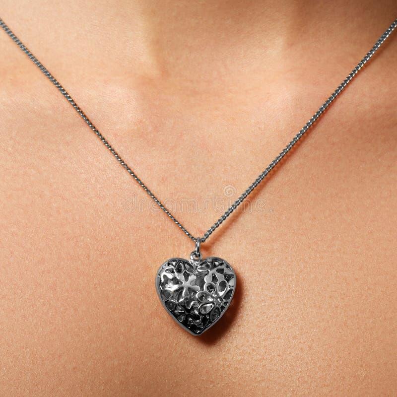 Pendente dourado do coração Beleza e conceito da joia Vestir da mulher fotografia de stock royalty free