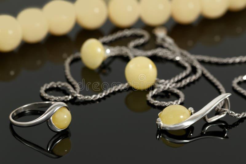 Pendente e anel de prata do close up com âmbar no fundo dos brincos e grânulos na placa preta fotografia de stock