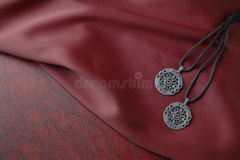Pendentes celtas no pano de seda vermelho no livro de couro imagens de stock