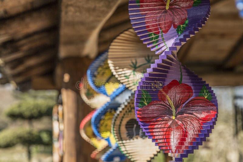 Pendentes do vento que destacam um com uma flor vermelha em um fundo roxo e violeta foto de stock