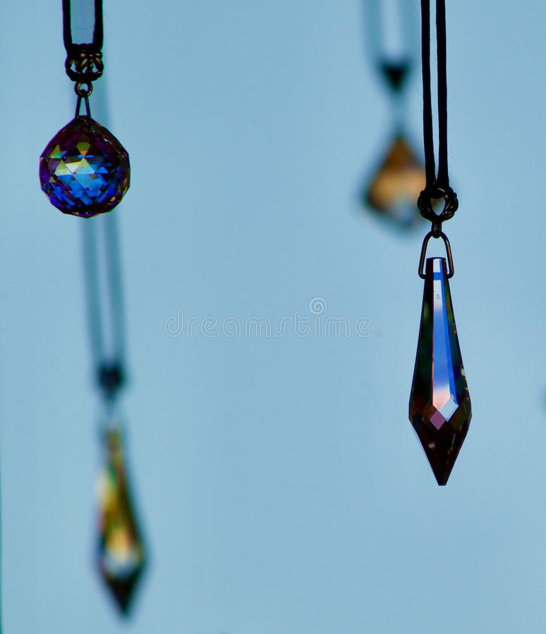 Pendents en cristal accrochant avec un fond bleu photo libre de droits