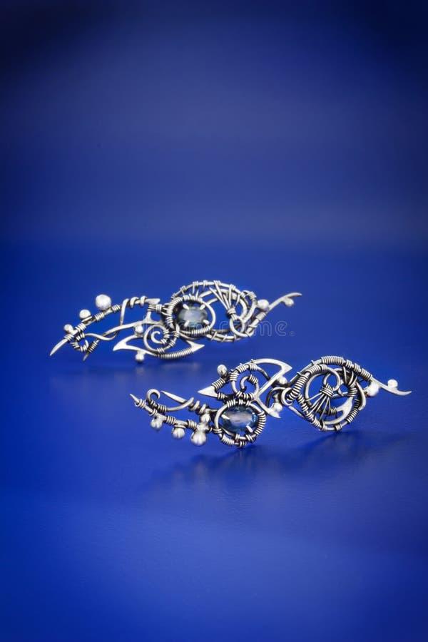 Pendientes azules de plata del abrigo del alambre del zafiro fotografía de archivo