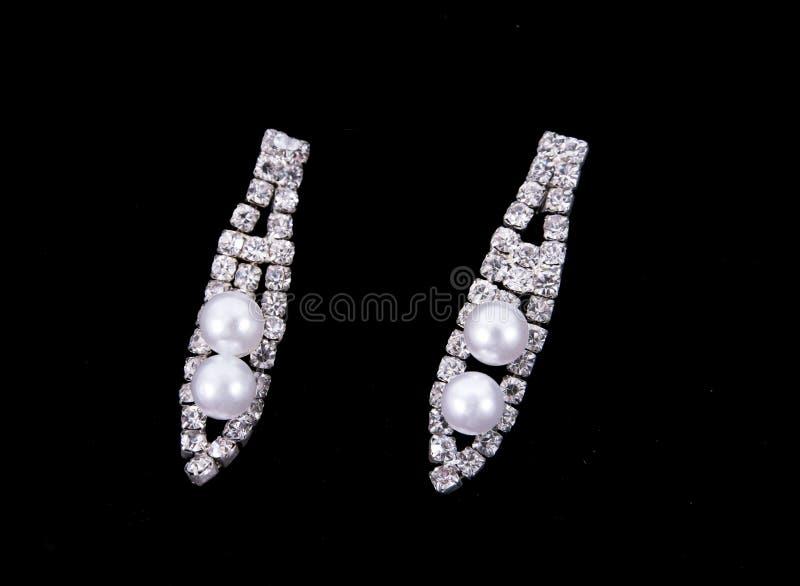 Pendientes con las perlas y diamantes aislados en fondo negro Pendiente de los diamantes aislado imagen de archivo libre de regalías