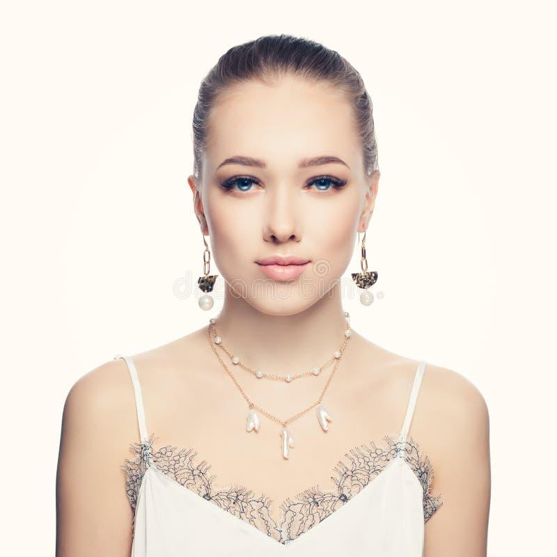 Pendientes de cadena de oro y collar hermosos de la moda de la mujer que llevan joven con el retrato blanco de las perlas foto de archivo