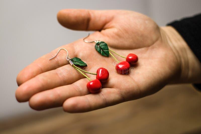 Pendientes de encargo hechos a mano de la arcilla del pol?mero de la cereza en fondo gris de la tela a mano imagen de archivo libre de regalías