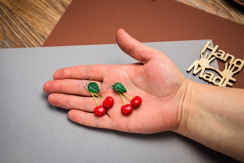 Pendientes de encargo hechos a mano de la arcilla del pol?mero de la cereza en fondo gris de la tela a mano fotografía de archivo libre de regalías