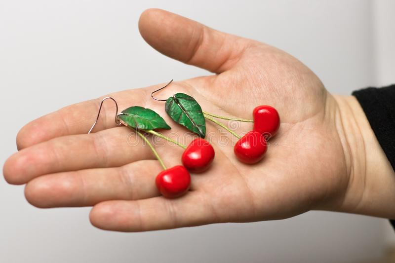 Pendientes de encargo hechos a mano de la arcilla del pol?mero de la cereza en fondo gris de la tela a mano fotos de archivo libres de regalías