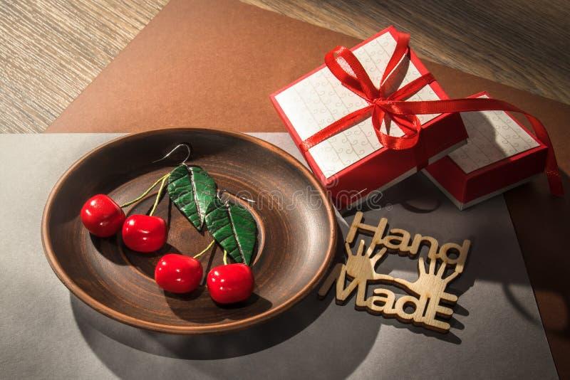 Pendientes de encargo hechos a mano de la arcilla del pol?mero de la cereza en la placa de madera imagen de archivo libre de regalías