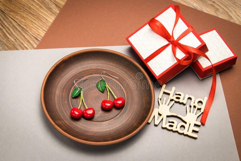 Pendientes de encargo hechos a mano de la arcilla del pol?mero de la cereza en la placa de madera imágenes de archivo libres de regalías