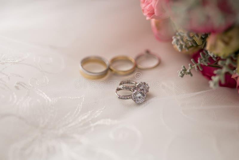 Pendientes de la boda del oro blanco con las piedras preciosas que mienten cerca de las flores y de los anillos imágenes de archivo libres de regalías
