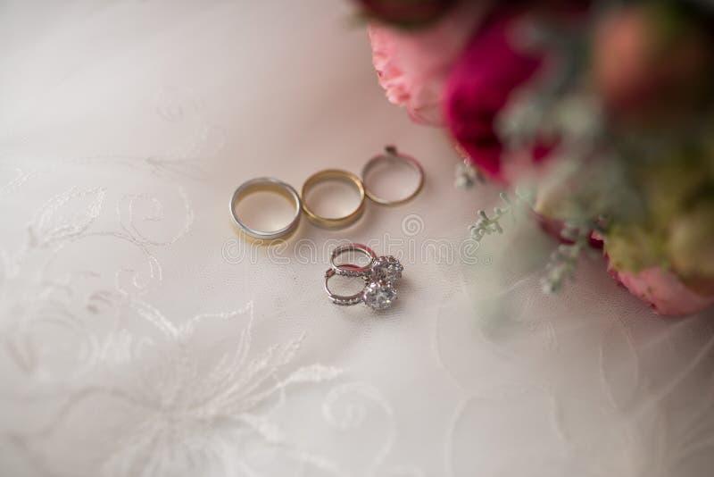 Pendientes de la boda del oro blanco con las piedras preciosas que mienten cerca de las flores y de los anillos Joyería y primer  foto de archivo