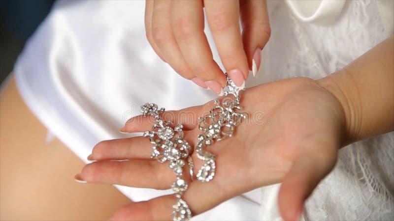 Pendientes de la boda en una mano nupcial, accesorios de la mañana y de la joyería del ` s de la novia y concepto de la decoració foto de archivo libre de regalías