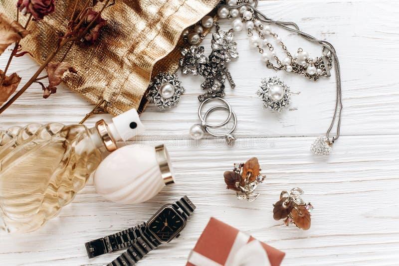 Pendientes de los anillos de la joyería y perfume y reloj costosos de lujo encendido foto de archivo