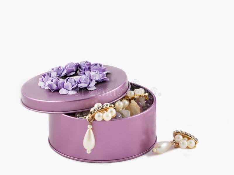 Pendientes de oro magníficos hermosos del primer en la caja violeta fotografía de archivo libre de regalías