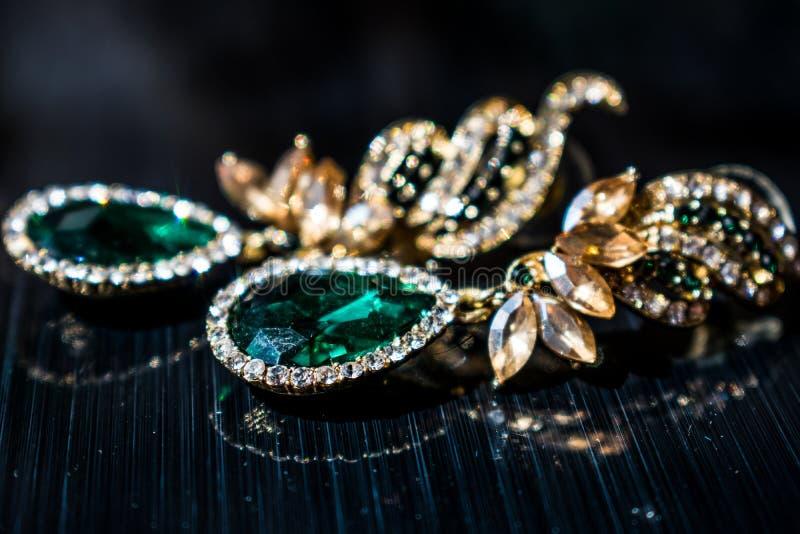 Pendientes del oro del metal con los diamantes artificiales verdes, esmeralda de las piedras, blancos y amarillos En un fondo bri foto de archivo