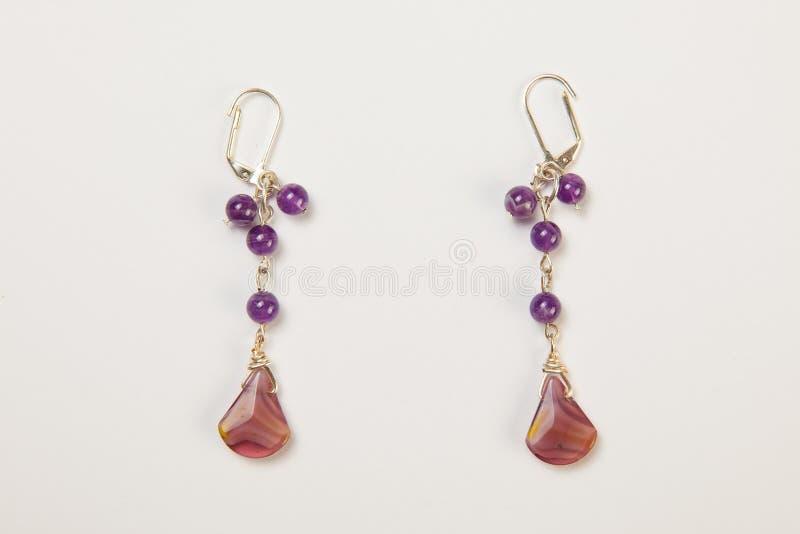 Pendientes hechos a mano hechos de cristales púrpuras de la gota imagen de archivo libre de regalías