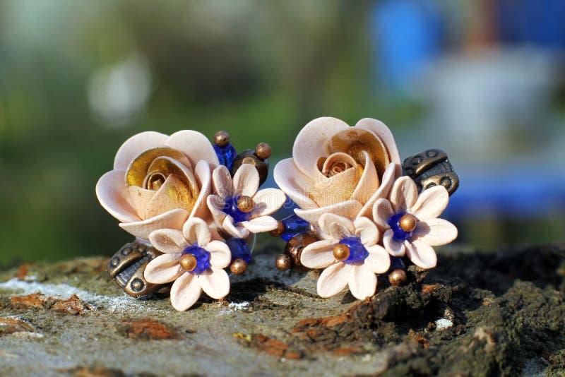 Pendientes hechos a mano en una forma de flores de la arcilla del pol?mero imágenes de archivo libres de regalías