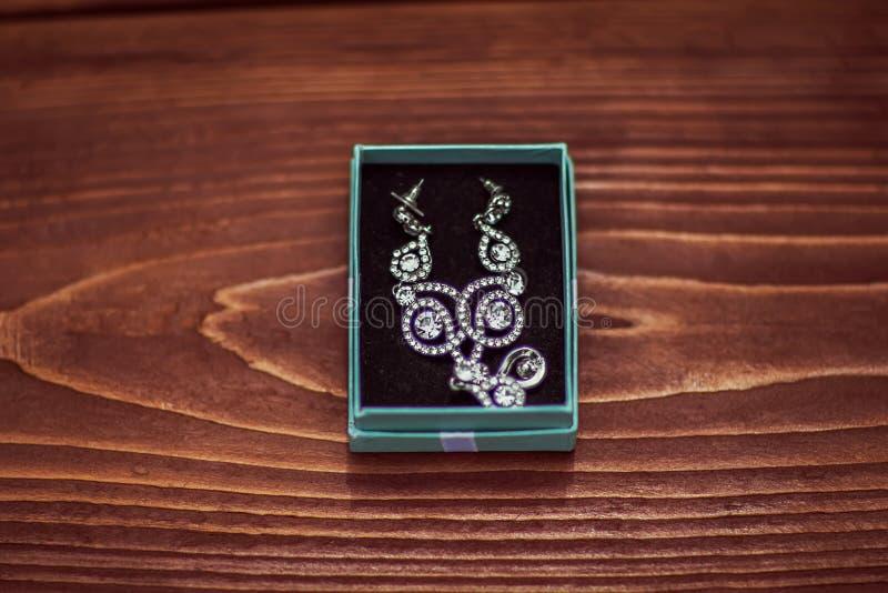 Pendientes hermosos de la novia con las piedras en la caja azul, complementos, casandose decoraciones en un fondo de madera marró imagen de archivo