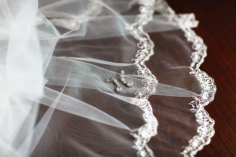 Pendientes para las novias con el cordón blanco, complementos, casandose decoraciones en fondo de madera marrón fotos de archivo