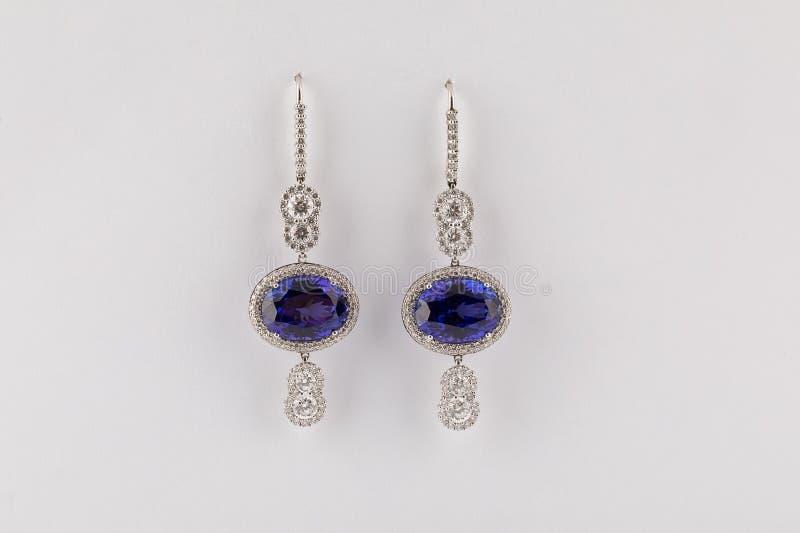Pendientes para mujer de plata con el diamante azul grande aislado en el fondo blanco imagen de archivo