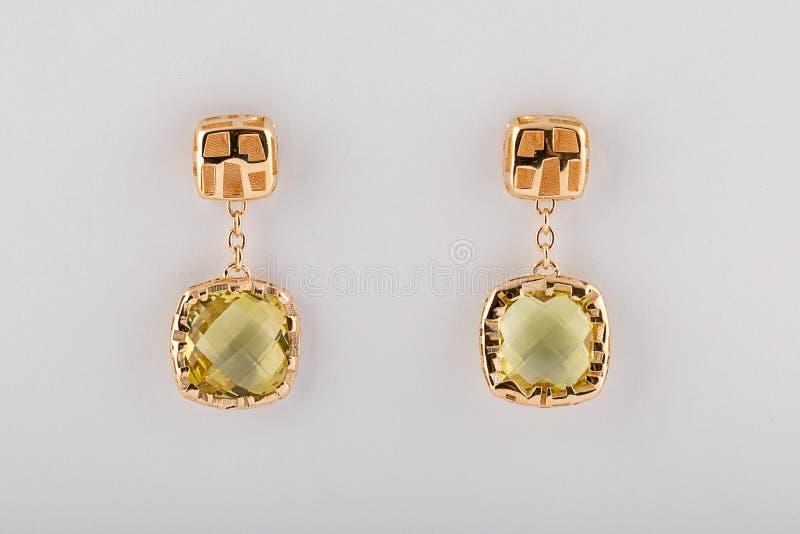 Pendientes para mujer del oro con el diamante amarillo claro aislado en el fondo blanco imagen de archivo