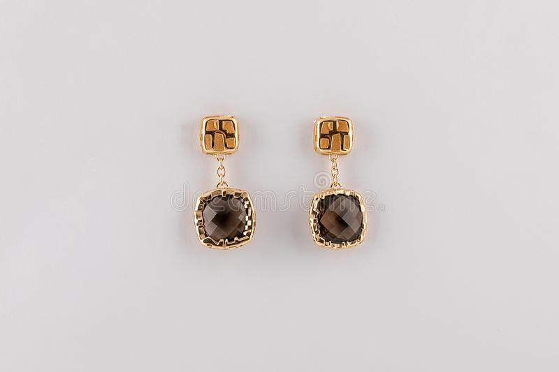 Pendientes para mujer del oro con el diamante negro en el fondo blanco imágenes de archivo libres de regalías