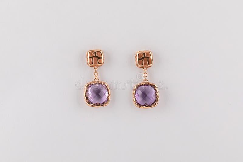 Pendientes para mujer del oro con el diamante púrpura aislado en el fondo blanco fotografía de archivo libre de regalías