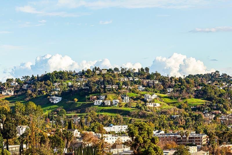Pendii di collina erbosi verdi in autunno con la palma e gli alberi con le case con cielo blu e le nuvole fotografia stock