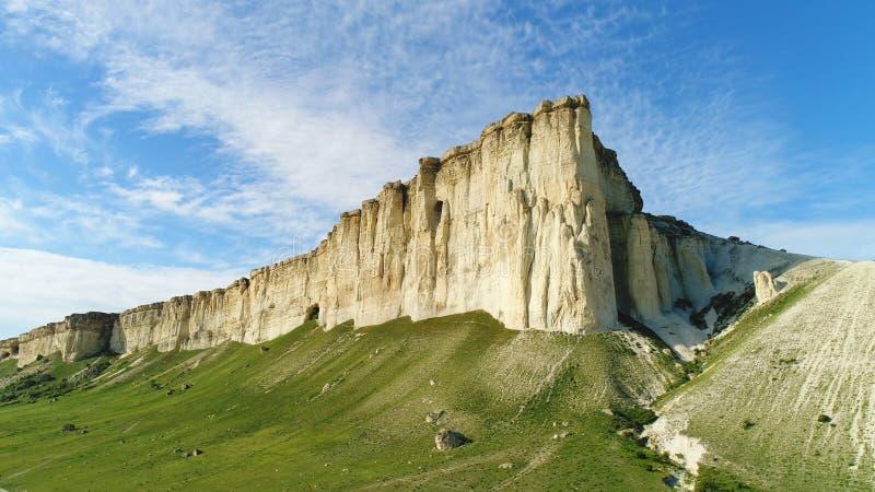 Pendio bianco pittoresco, pietre e colline della scogliera vicino al bello prato verde contro il cielo nuvoloso blu nel giorno di immagine stock