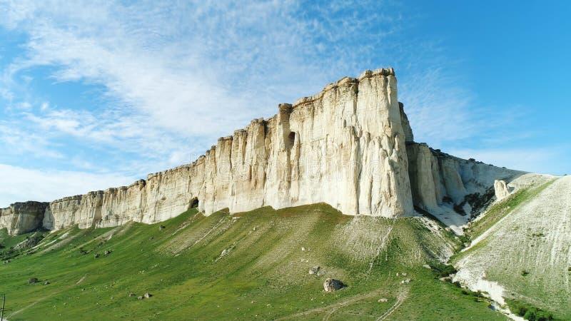 Pendio bianco pittoresco, pietre e colline della scogliera vicino al bello prato verde contro il cielo nuvoloso blu nel giorno di fotografia stock