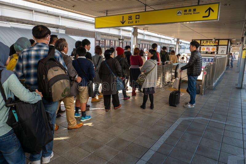 Pendler stehen oben in der Linie an, um die Himeji-Station herauszunehmen stockfotografie