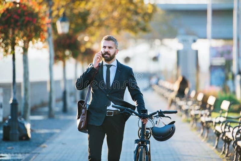 Pendolare dell'uomo d'affari con la bicicletta che cammina a casa dal lavoro in città, facendo uso dello smartphone immagini stock libere da diritti