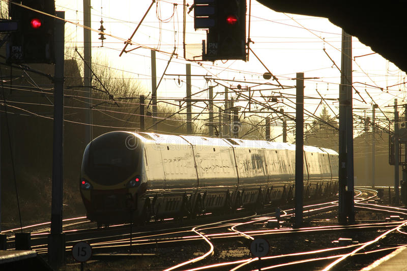 Pendolino electric train in evening light on WCML. Evening sunlight catches the side of a pendolino electric multiple unit train as it passes through Carnforth stock photo