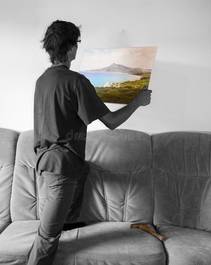 Pendurando uma pintura colorida na parede branca vazia foto de stock