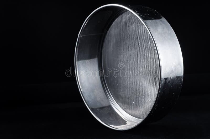 Peneira de aço inoxidável para peneirar o cereal em um fundo preto foto de stock royalty free