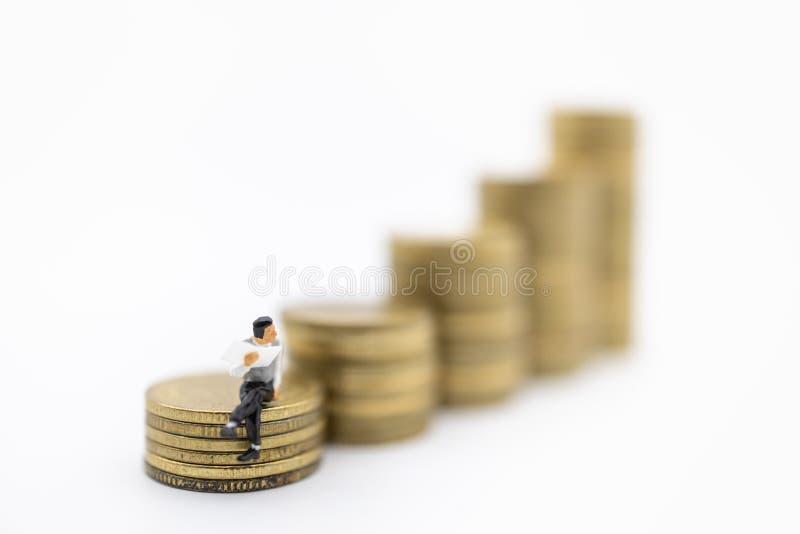 Pengar affär, besparing- och planerabegrepp Stäng sig upp av affärsmanminiatyrdiagramet perople som sitter på och läser en tidnin royaltyfri bild