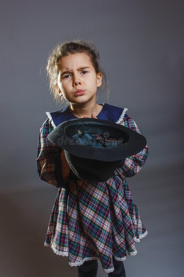 Pengar för flickabarntiggaren precis för mat håller hans royaltyfri fotografi