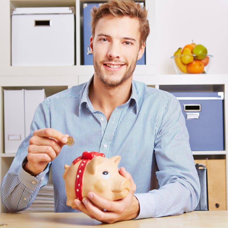 Pengar för manbesparingeuroen i piggy packar ihop arkivfoton