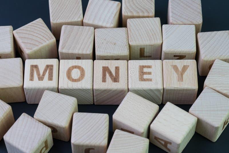 Pengar-, finans- eller besparingbegrepp vid kubträkvarteret med alfabetet som bygger ordpengarna på mitten på den mörka svart arkivbilder