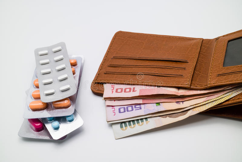 Pengar i brun plånbok med blåsor av preventivpillerar royaltyfri fotografi
